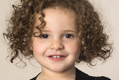 Smiling toddler with brown curly at a Preschool & Childcare Serving Salt Lake City, UT